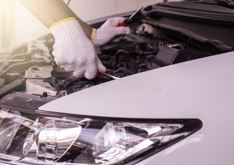 Primer de la batería de coche de la fijación del ingeniero del mecánico de la mano en el garaje fotos de archivo libres de regalías