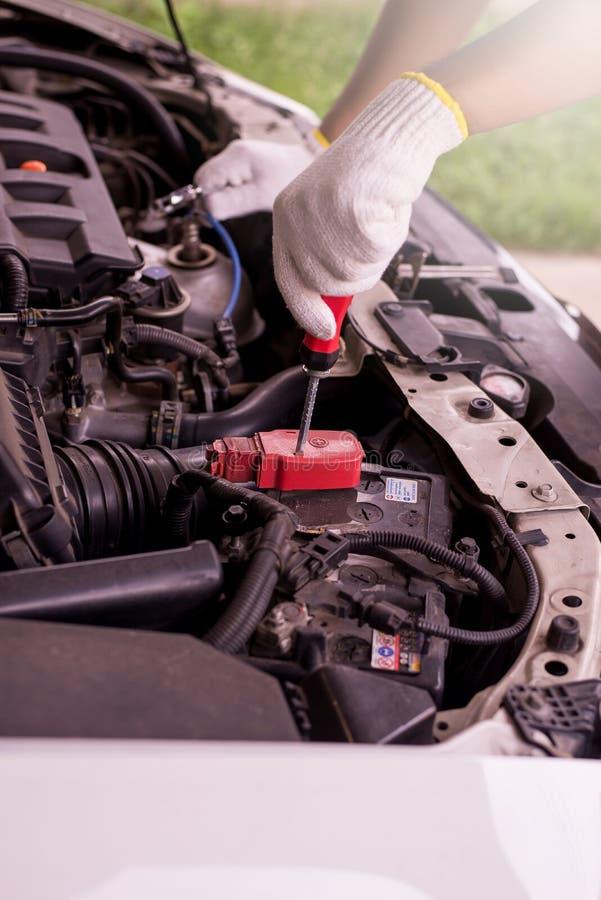 Primer de la batería de coche de la fijación del ingeniero del mecánico de la mano en el garaje imagenes de archivo