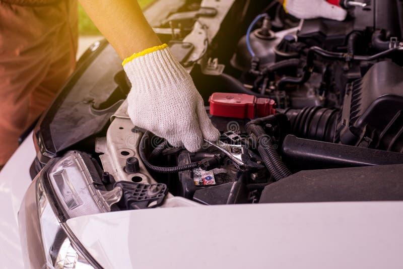Primer de la batería de coche de la fijación del ingeniero del mecánico de la mano en el garaje fotografía de archivo