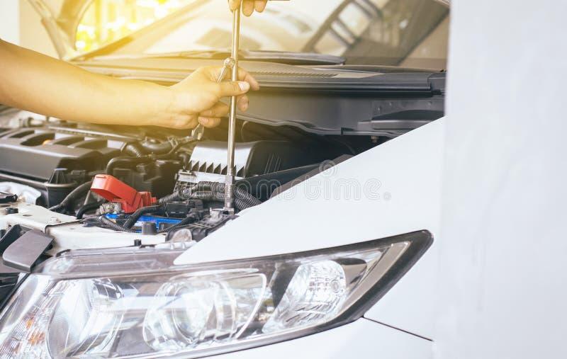 Primer de la batería de coche de la fijación del ingeniero del mecánico de la mano en el garaje, mantenimiento del coche del conc fotos de archivo libres de regalías
