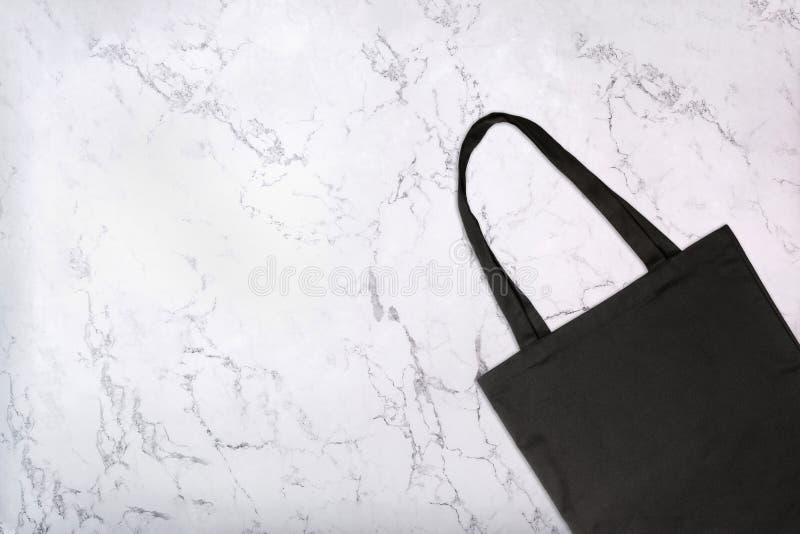 Primer de la bolsa de asas negra en la textura de mármol blanca Bolso que hace compras reutilizable del espacio en blanco en el f imagenes de archivo