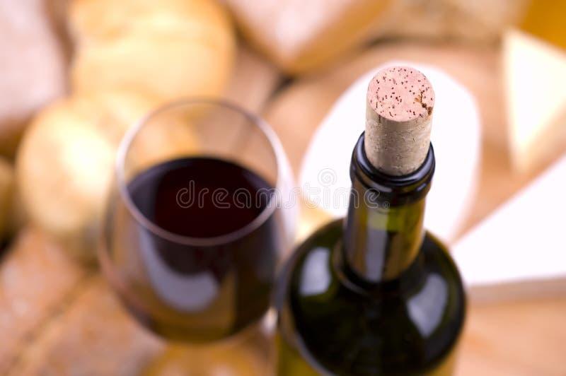 Primer de la botella de vino con el alimento y el vidrio fotografía de archivo