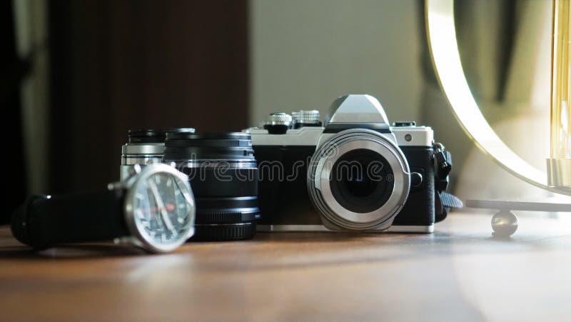 Primer de la cámara clásica en un escritorio de madera con el foco seleccionado equipo del reloj y de la lente Fondo con un hermo fotos de archivo libres de regalías