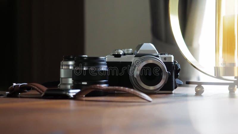 Primer de la cámara clásica en un escritorio de madera con el reloj digital y len el foco seleccionado equipo Fondo con un hermos fotos de archivo