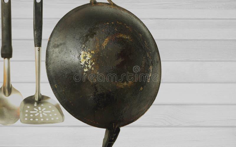 Primer de la cacerola y de los utensilios oxidados viejos que cuelgan en la pared fotos de archivo libres de regalías