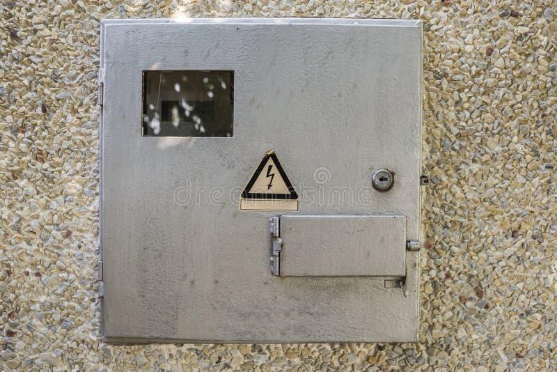 Primer de la caja azul clara del metro del metal eléctrico bloqueado con la muestra de cuidado de la precaución afuera en la pare fotografía de archivo