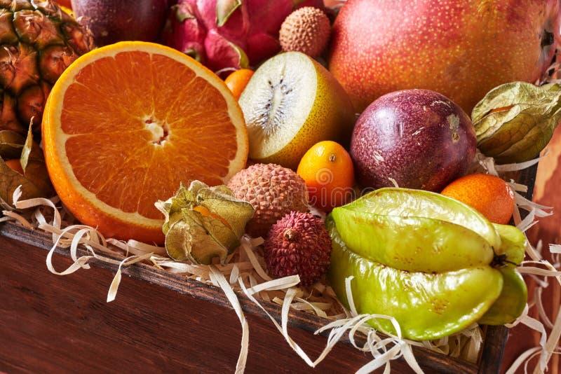 Primer de la caja con el carambola sano de las frutas frescas, a medias anaranjado, kiwi, pitahaya, fruta de la pasión, kumquat e imagenes de archivo