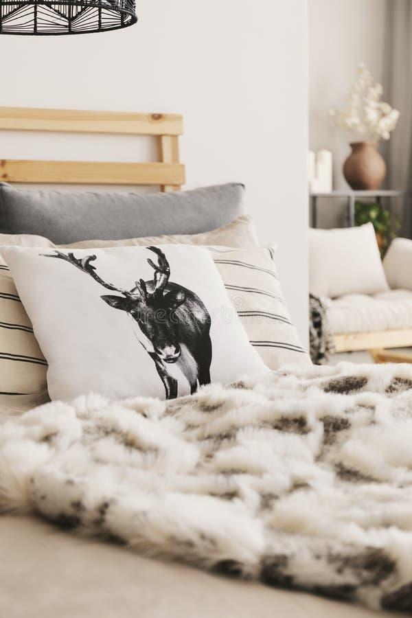Primer de la cama con el amortiguador del reno, muchas almohadas y situación de la sobrecama de la piel en el interior plano blan foto de archivo