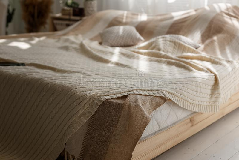 Primer de la cama matrimonial de la comodidad con las almohadas y la manta beige, de los haces del sol y de las sombras en dormit imagen de archivo