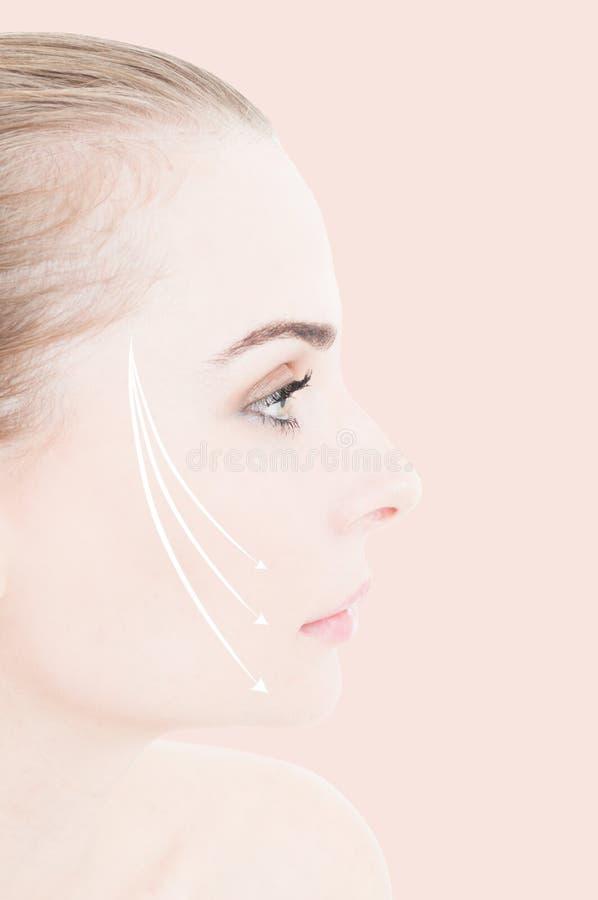 Primer de la cara de la mujer con las flechas de elevación en su mejilla fotos de archivo libres de regalías