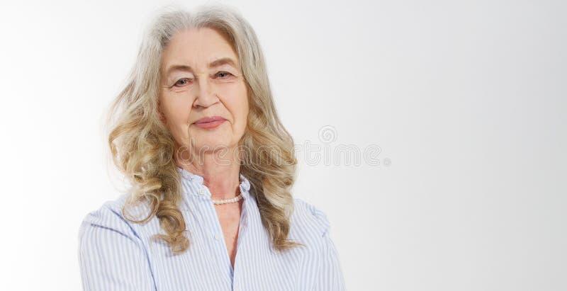 Primer de la cara mayor sonriente de la arruga de la mujer y del pelo gris Vieja señora madura que toca su piel arrugada aislada  fotos de archivo