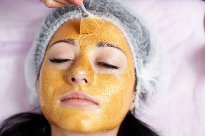 Primer de la cara de un cliente femenino de un salón de belleza con una máscara del oro encendido Cosmetología y rutina del cuida fotos de archivo libres de regalías