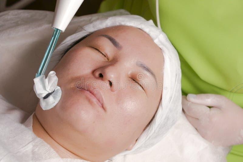 Primer de la cara de una mujer musulmán en el procedimiento facial del rejuvenecimiento de la fisioterapia Activación de la circu imagen de archivo libre de regalías