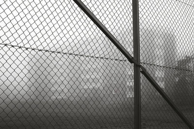 Primer de la cerca de alambre con la construcción de viviendas en el fondo imagenes de archivo