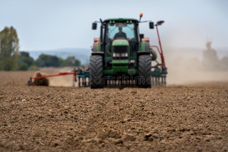 Primer de la cosecha con el campo de arado del tractor imagen de archivo libre de regalías