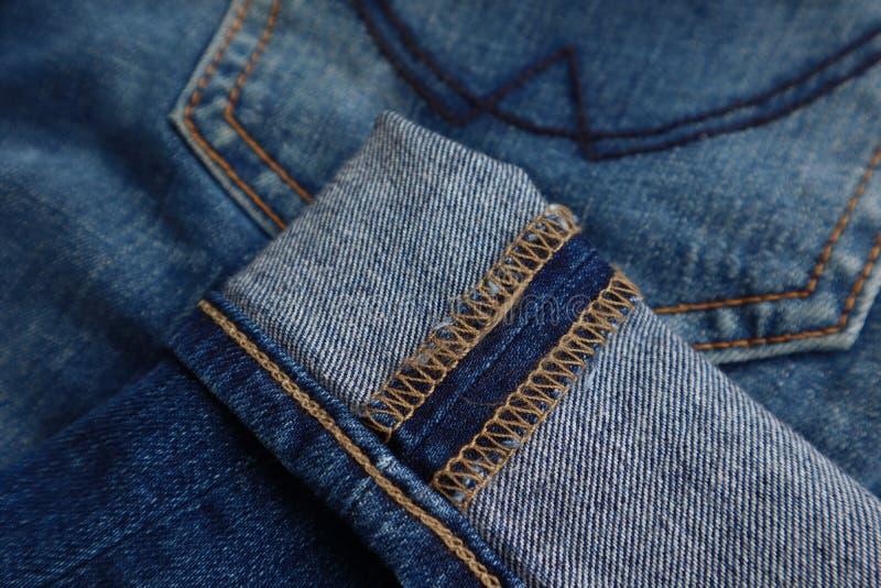 Primer de la costura en el puño de los vaqueros azules del dril de algodón imagenes de archivo