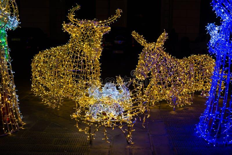 Primer de la escena de la natividad de la Navidad iluminada con las luces coloreadas fotografía de archivo libre de regalías