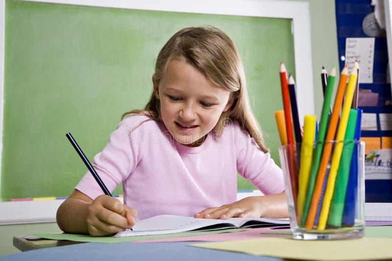 Primer de la escritura de la muchacha de la escuela en cuaderno fotos de archivo libres de regalías