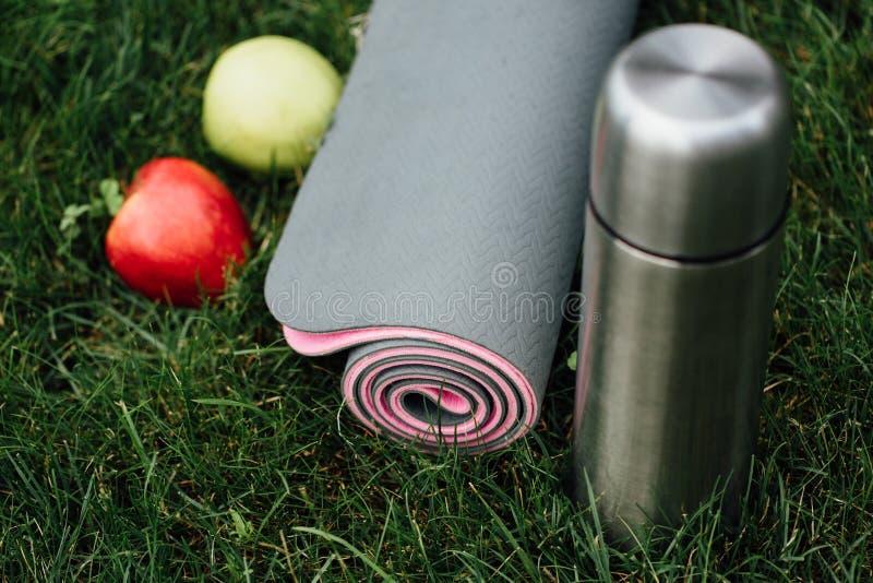 Primer de la estera rodada gris-rosada atractiva de la yoga o de la aptitud con las manzanas y termo en el parque en una hierba foto de archivo
