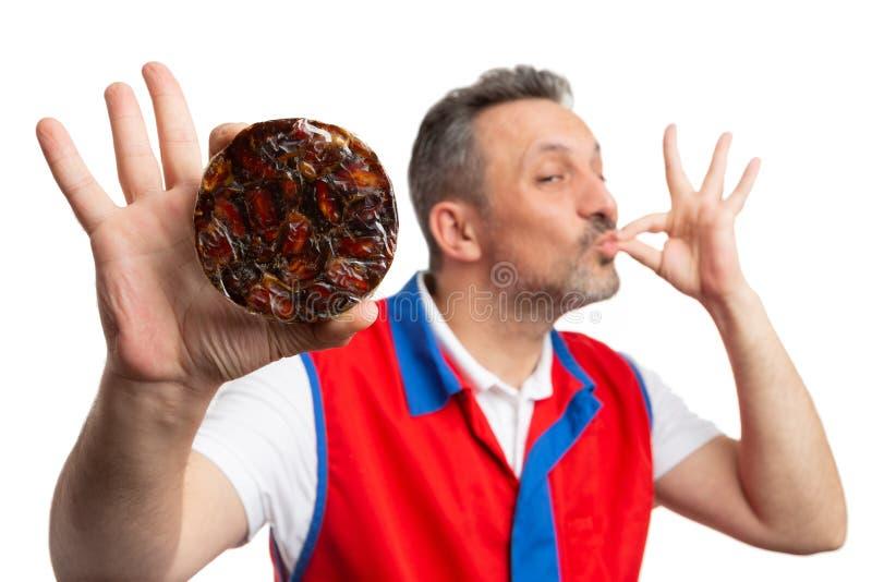 Primer de la fruta secada de la palma sostenida por las yemas del dedo que se besan del empleado imagen de archivo libre de regalías