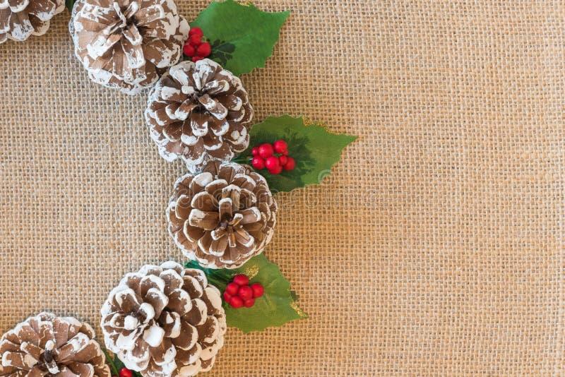 Primer de la guirnalda puesta plana de la Navidad de pinecones, de bayas rojas, y de hojas del acebo en fondo rústico de la tela imagen de archivo libre de regalías