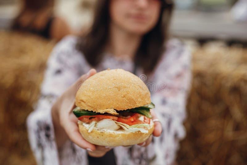 Primer de la hamburguesa del vegano en manos de la muchacha del boho Muchacha elegante del inconformista en gafas de sol que come foto de archivo libre de regalías