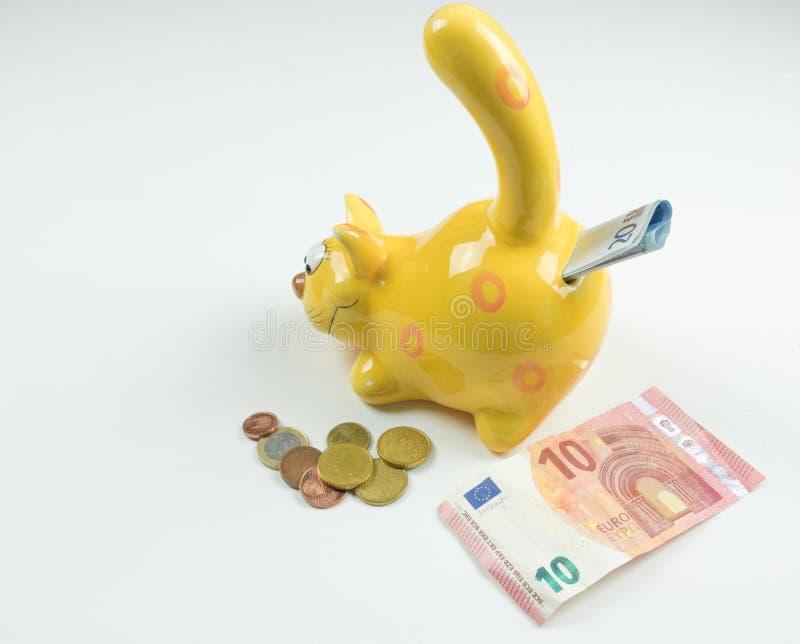 Primer de la hucha, dinero y conceptos financieros El dinero de los países diferentes se fotografía aislador foto de archivo libre de regalías