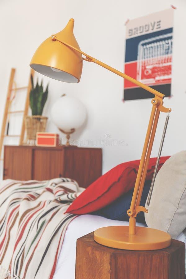 Primer de la lámpara anaranjada en la mesita de noche en el dormitorio del vintage, foto real fotos de archivo