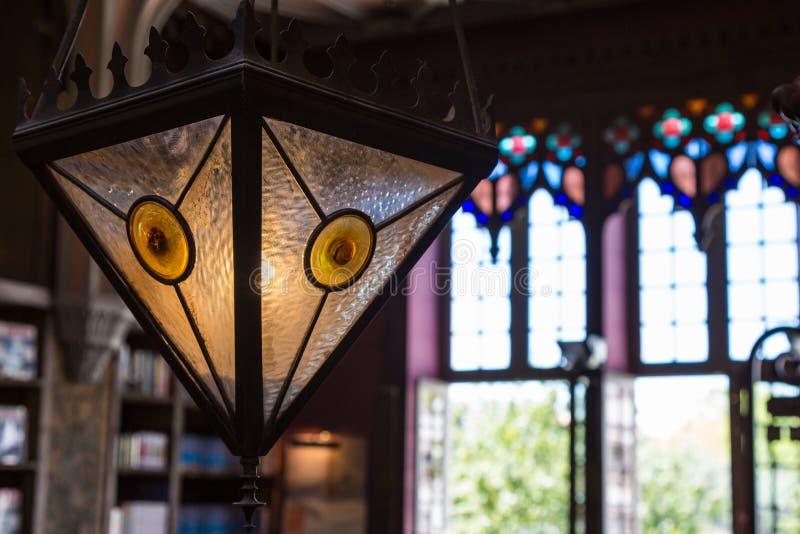 Primer de la lámpara de cristal colorida antigua en librería fotos de archivo