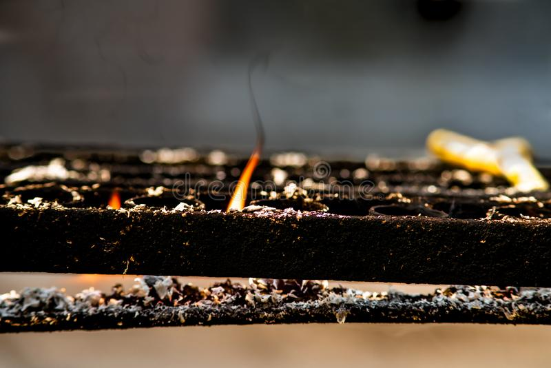 Primer de la llama anaranjada de la vela ardiendo en tenedor negro de la palmatoria del metal en un templo budista foto de archivo