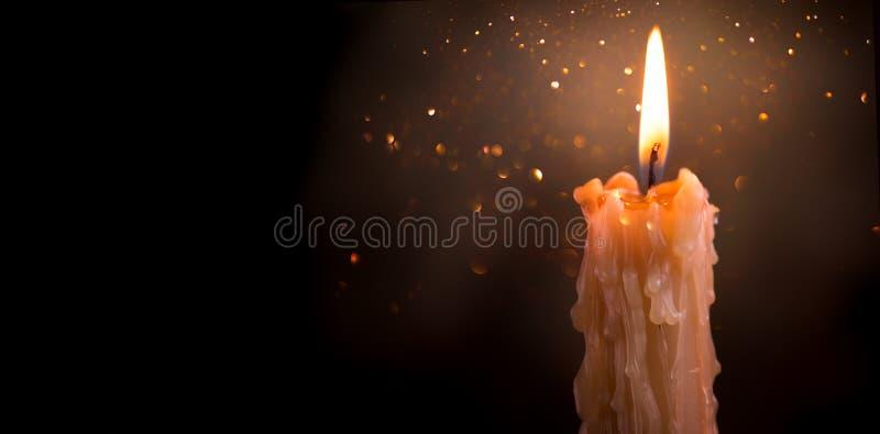 Primer de la llama de vela en un fondo oscuro Diseño de la frontera de la luz de la vela Vela derretida de la cera que quema en l fotografía de archivo