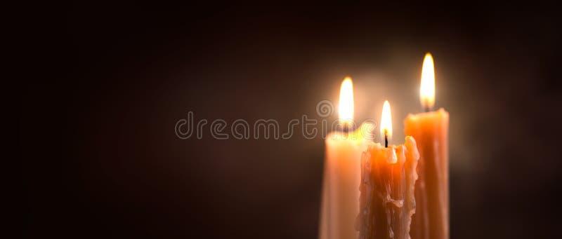 Primer de la llama de vela en un fondo oscuro Diseño de la frontera de la luz de la vela Velas derretidas de la cera que queman e imagen de archivo