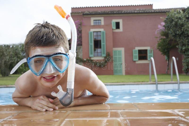 Primer de la máscara que bucea que lleva del muchacho en piscina fotos de archivo
