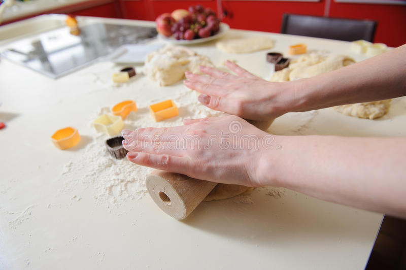 Primer de la mano de la mujer con las galletas de la hornada del balanceo foto de archivo