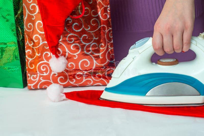 Primer de la mano de la mujer que plancha el sombrero de la Navidad en el backgr fotos de archivo