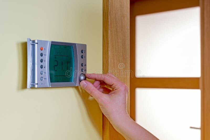 Primer de la mano de una mujer que fija la temperatura ambiente en un modo imagen de archivo libre de regalías