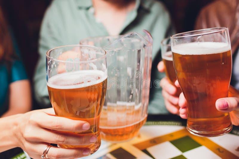 Primer de la mano del camarero en el golpecito de la cerveza que vierte una cerveza de cerveza dorada del proyecto imagenes de archivo