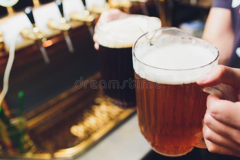 Primer de la mano del camarero en el golpecito de la cerveza que vierte una cerveza de cerveza dorada del proyecto foto de archivo libre de regalías
