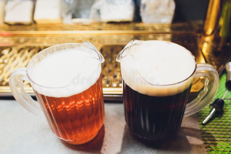 Primer de la mano del camarero en el golpecito de la cerveza que vierte una cerveza de cerveza dorada del proyecto fotografía de archivo libre de regalías