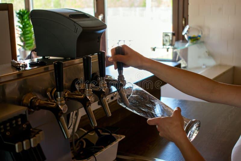Primer de la mano del camarero en el golpecito de la cerveza que vierte una cerveza de cerveza dorada del proyecto foto de archivo