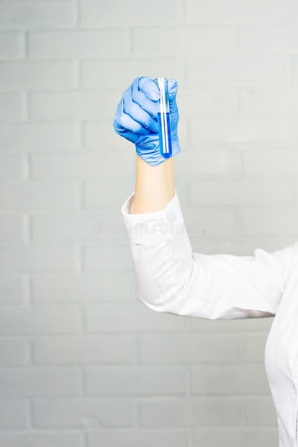 Primer de la mano del investigador de sexo femenino médico que sostiene el tubo de ensayo con el líquido azul foto de archivo libre de regalías