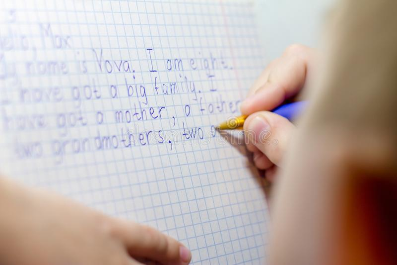 Primer de la mano del muchacho con el lápiz que escribe palabras inglesas a mano en el papel blanco tradicional de la libreta fotos de archivo libres de regalías