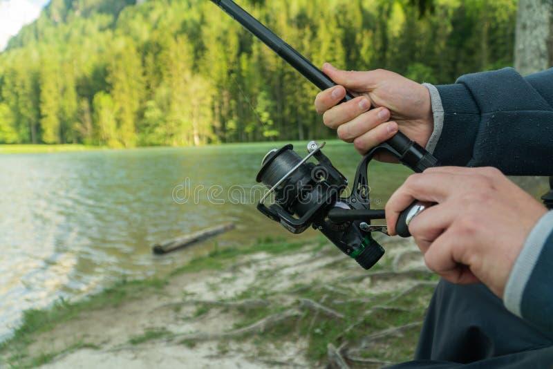 Primer de la mano del pescador s con el giro - temporada de pesca del verano fotos de archivo