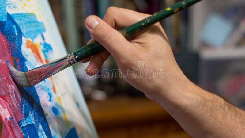 Primer de la mano del ` s del hombre que pinta una imagen o del extracto del acrílico o del aceite imagen de archivo libre de regalías