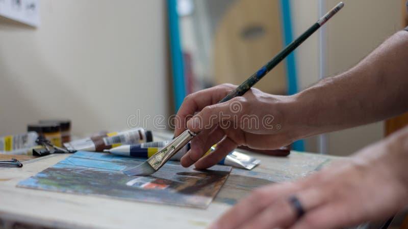 Primer de la mano del ` s del hombre que pinta una imagen o de la pintura del acrílico o de aceite imagen de archivo libre de regalías