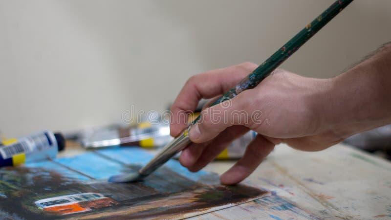 Primer de la mano del ` s del hombre que pinta una imagen o de la pintura del acrílico o de aceite imagenes de archivo