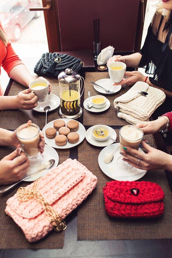 Primer de la mano del ` s de la muchacha que sostiene té y capuchino En té de la mentira de la tabla, miel, capuchino, macarrones imágenes de archivo libres de regalías