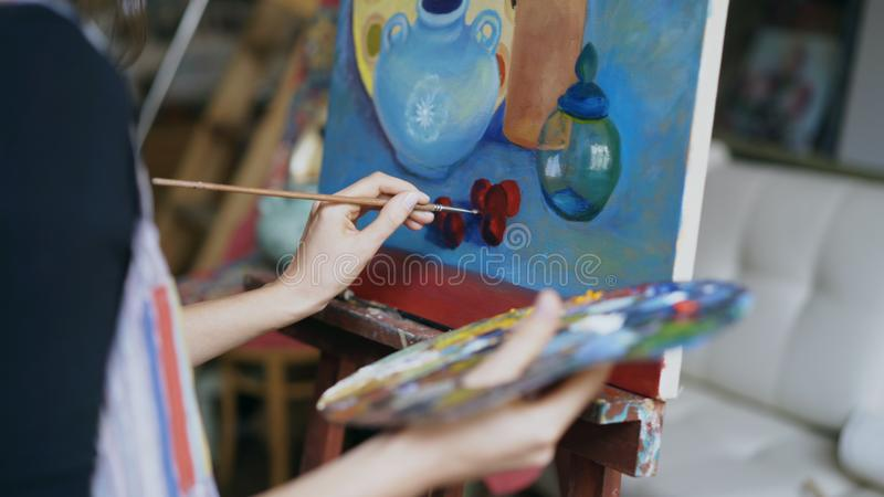 Primer de la mano del ` s de la mujer del artista con el cepillo todavía que pinta la imagen de la vida en lona en estudio del ar fotos de archivo
