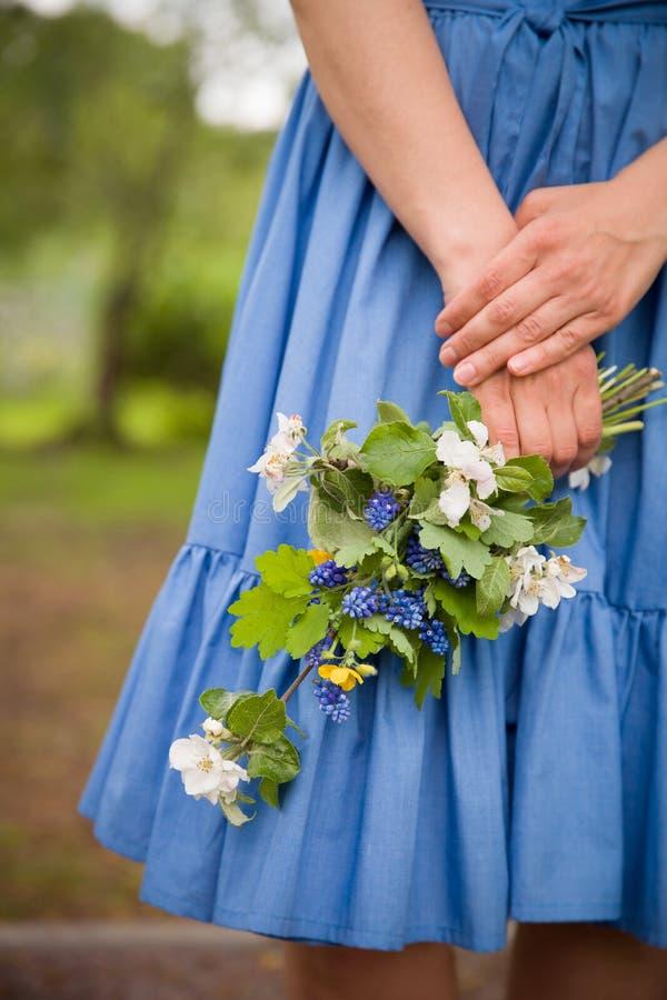 Primer de la mano del ` s de la mujer que lleva a cabo una rama del manzano floreciente Vestido de los azules como fondo Concepto imagen de archivo libre de regalías