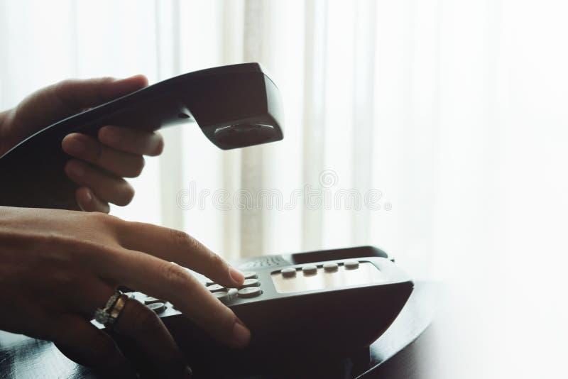 Primer de la mano del ` s de la mujer usando un teléfono en nea de la casa o del hotel imagenes de archivo